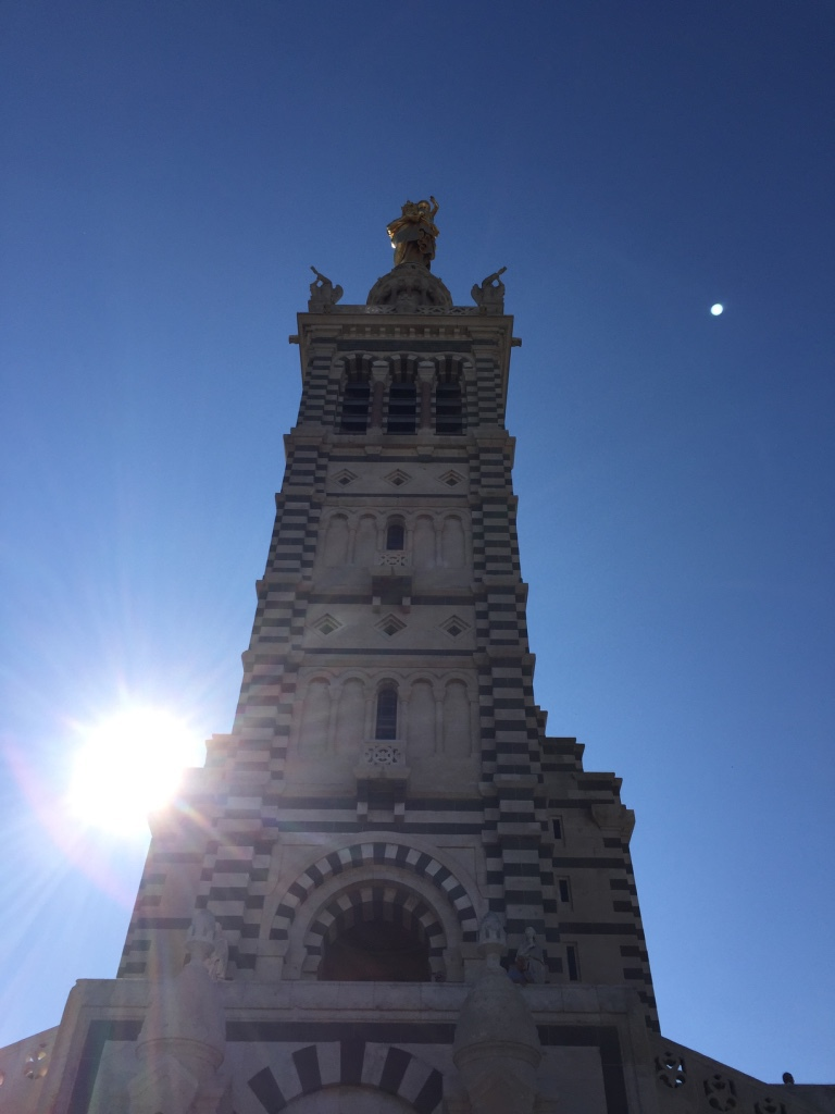 The bell-tower topped with statue of Notre-Dame, with the sun and the moon in the background