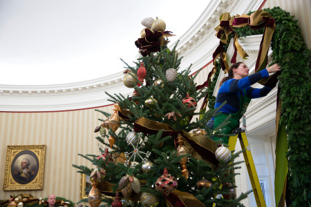 White_House_volunteers_hang_Christmas_decorations_in_the_Oval_Office